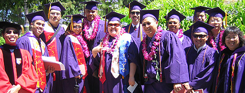 Asian American Studies students dressed in cap and gown for graduation with flower leis