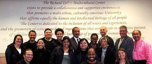 Photo of faculty and students in front of the writing on the wall in the Richard Oakes Multicultural Center which speaks about the goals of the center.